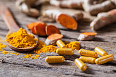 Turmeric powder, turmeric capsule and turmeric on wooden background