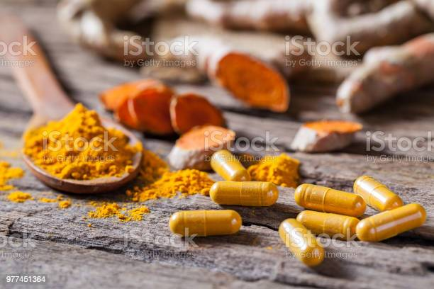 Turmeric Powder Turmeric Capsule And Turmeric On Wooden Background Stock Photo - Download Image Now
