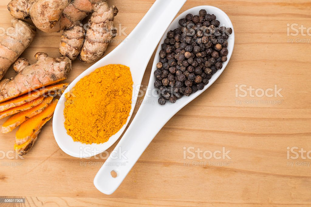 Turmeric roots and black pepper combination enhances curcumin ab stock photo