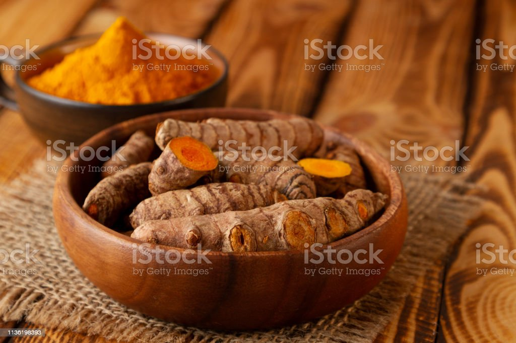 Turmeric roots and powder on wooden background. Selective focus on...