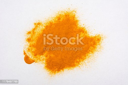 Ground turmeric spice pile on a white background