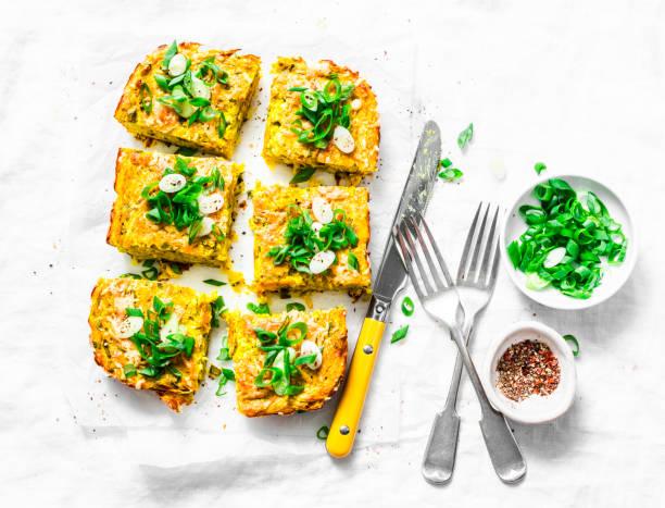 kurkuma, zucchini, pürierte kichererbsen tortilla mit kräutern auf einem hellen hintergrund, ansicht von oben. leckere vorspeise oder snack - kartoffel frittata stock-fotos und bilder