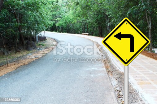 Turn left warning sign on a curve road