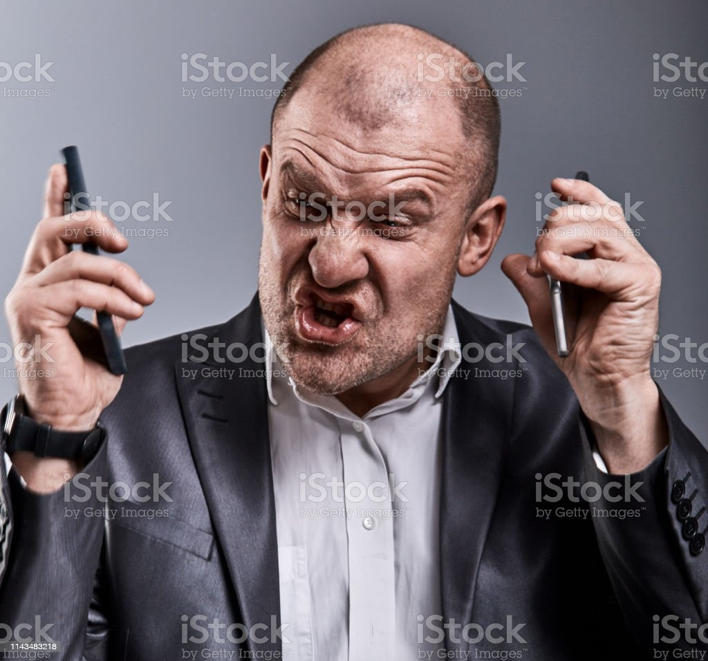 Turn nasty loud crying angry business man talking on two mobile phone very emotional in office suit on grey background. Closeup royalty-free stock photo