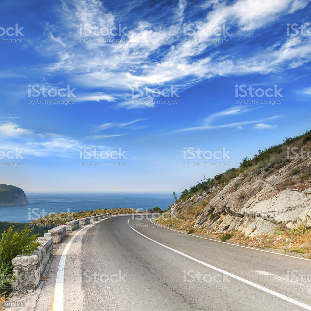 Turn of mountain highway with dramatic blue sky and sea stock photo