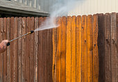 Spraying the top of a Wooden fence spraying a high Pressure washing a dirty grimy old wooden fence and turning it from dirty to clean in a matter of second with spray blast from pressure washer