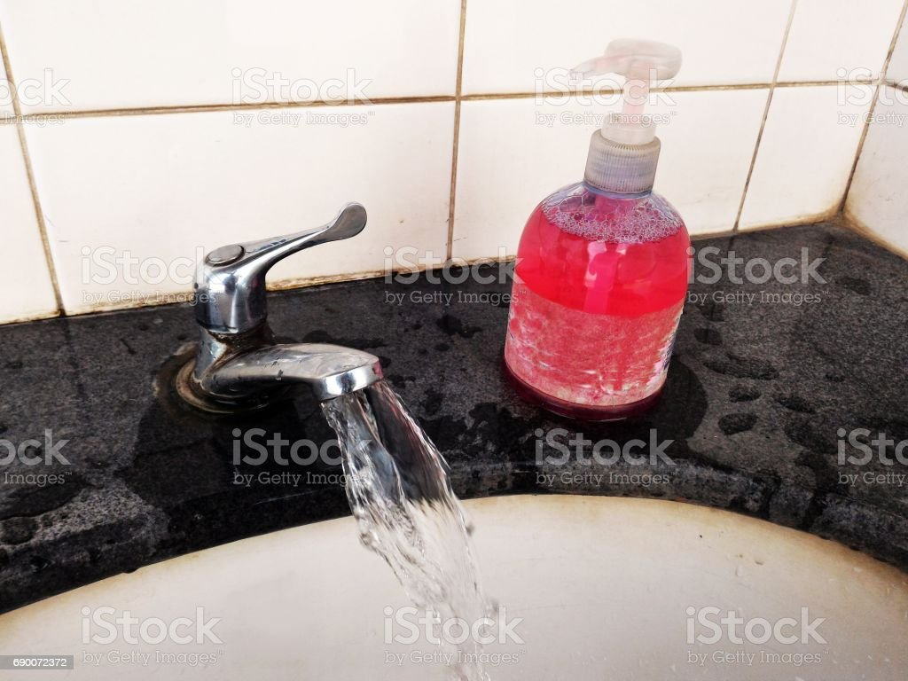 Turn On Faucet Beside Old Pink Shampoo Bottle Stock Photo & More ...