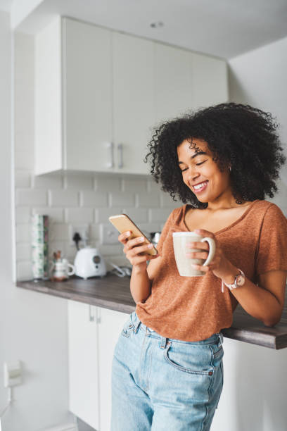 Turn on the day with coffee and social media Shot of a young woman using a smartphone and having coffee in the kitchen at home modern lifestyle stock pictures, royalty-free photos & images