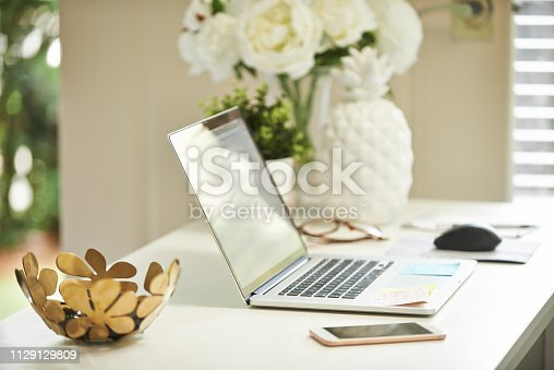 Shot of a laptop on a desk in a home study