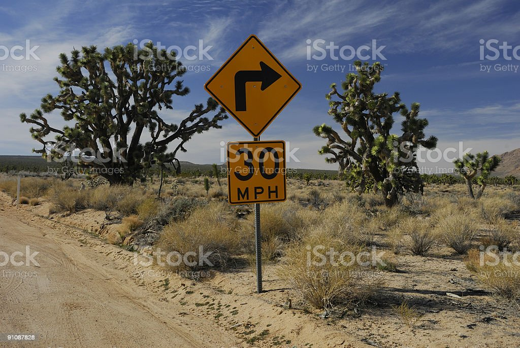Turn sign on desert road royalty-free stock photo