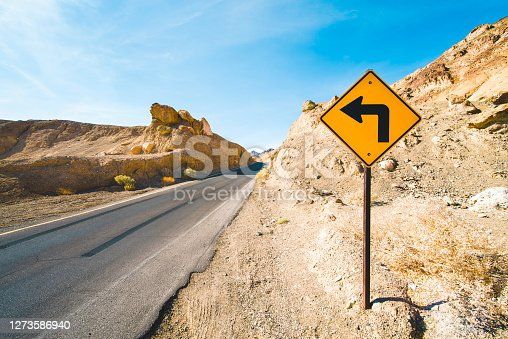 Driving on a straight asphalt road in Death Valley National Park when a turn sign suddenly shows up, California, USA.