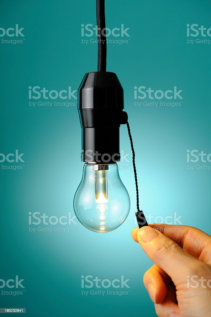 Turn the LED light bulb on or off with finger stock photo