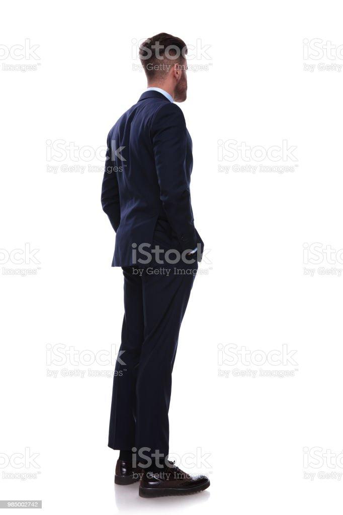 hombre de negocios dado vuelta en traje azul marino se ve al lado foto de stock libre de derechos