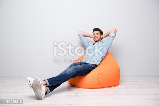 Turned full length body size photo of cheerful confident, relaxing man sitting in chair thinking guessing smiling toothily having rest fun isolated over grey color background