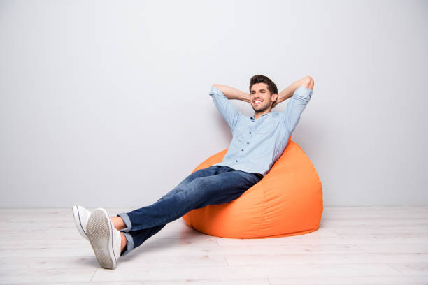 Convertido de longitud completa tamaño del cuerpo foto de alegre hombre relajante confiado sentado en la silla pensando adivinar sonriendo dentado teniendo el descanso divertido aislado sobre el fondo de color gris - foto de stock