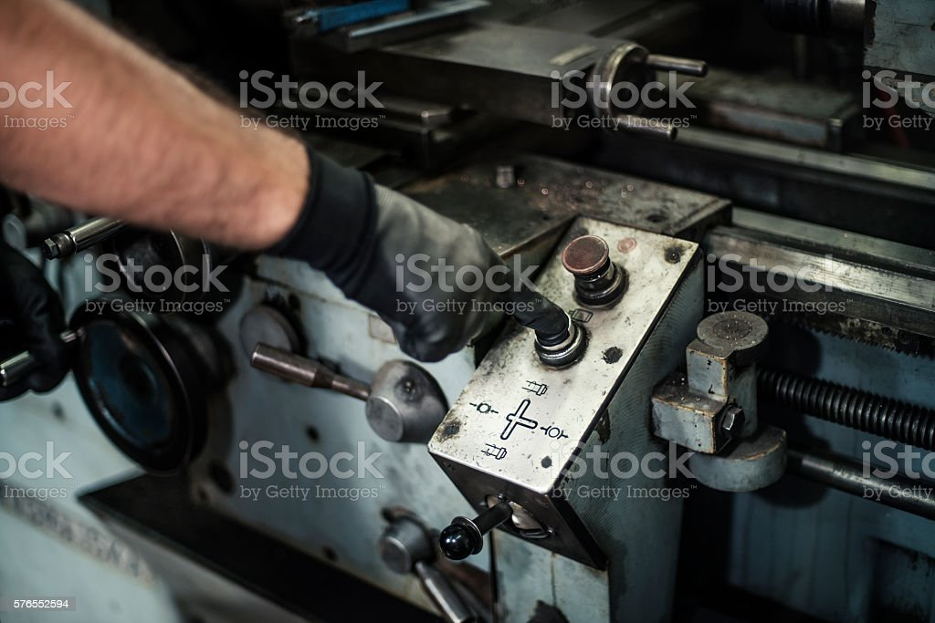 turner turning on the drill in a workshop stock photo