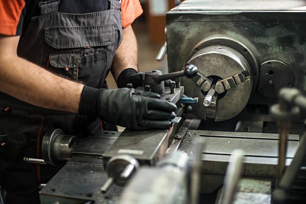 Turner worker working on drill bit in a workshop - Photo