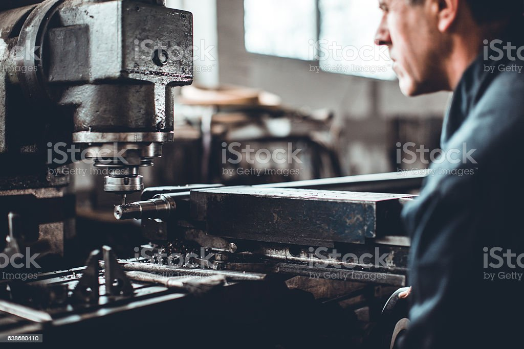 Turner worker working on drill bit in a workshop stock photo