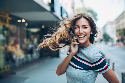 Smiling young woman with smart phone walking on the street and turning to look back, with copy space.