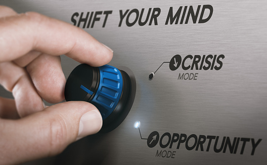 Man turning a knob to turn crisis into an opportunity. Composite image between a hand photography and a 3D background.