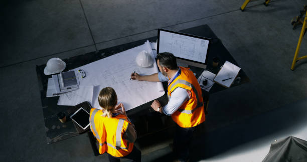 Turning dreams into winning designs High angle shot of two engineers going over a blueprint together in an industrial place of work engineering stock pictures, royalty-free photos & images