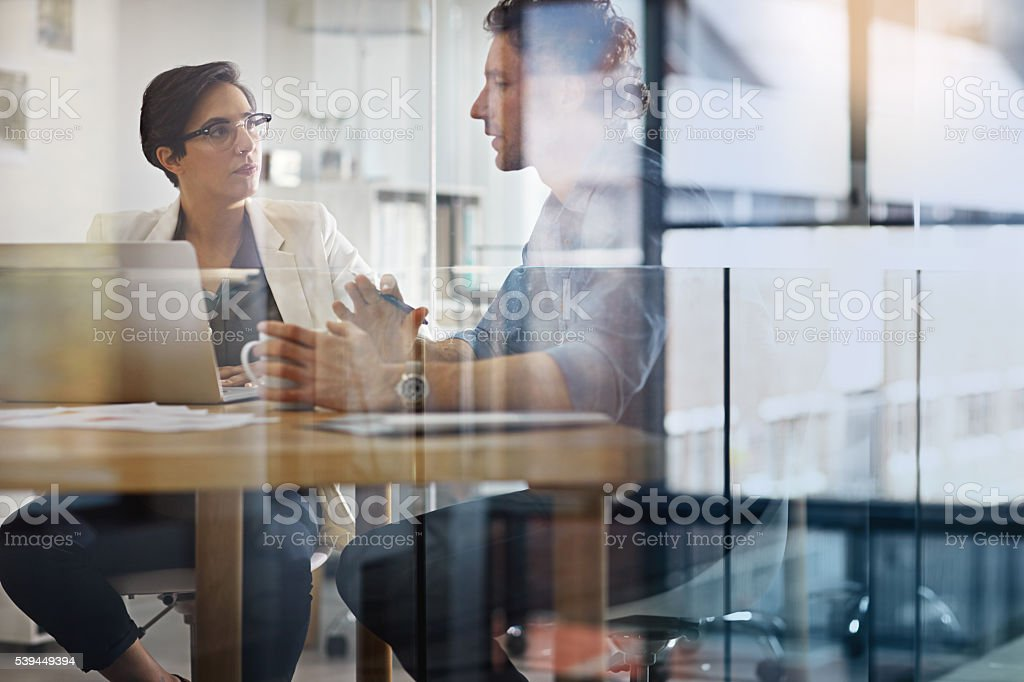 Shot of businesspeople working on a laptop in an office