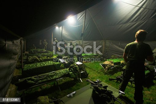 Soldiers getting ready to bunk down inside of their large tent