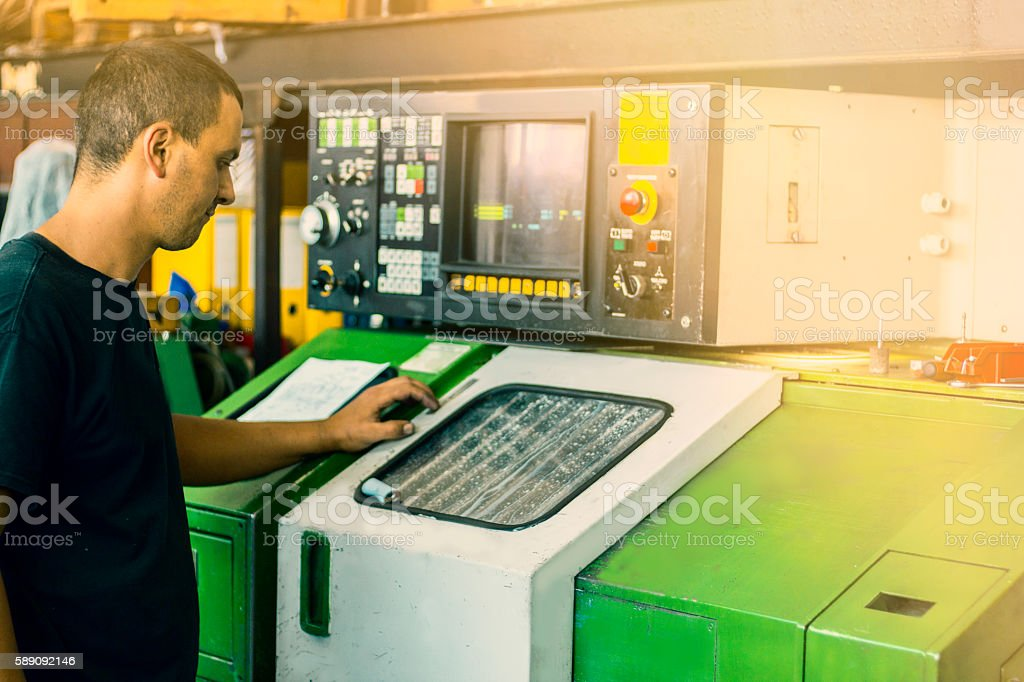 CNC turning machine operator. Worker performing a job at tool...