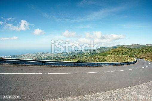 Turning mountain highway with blue sky and sea on a background. A curvy road through the grassy hills with a view of the ocean.