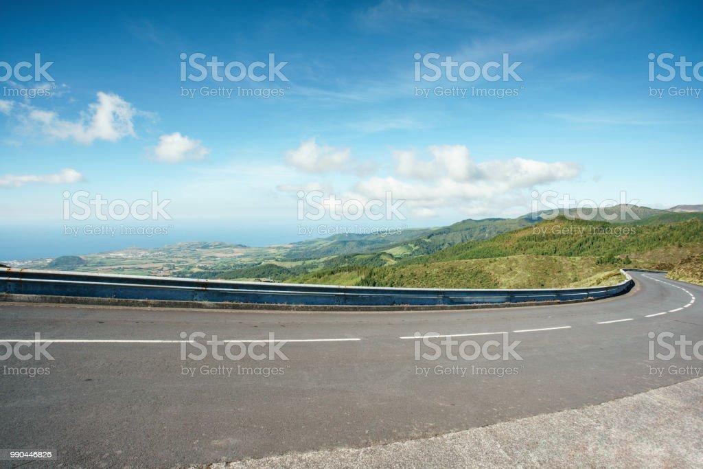 Berg-Autobahn mit blauem Himmel und Meer auf einem Hintergrund drehen. Eine kurvenreiche Straße durch die grasbewachsenen Hügel mit Blick auf den Ozean. Sao Miguel, Azoren. Portugal. – Foto