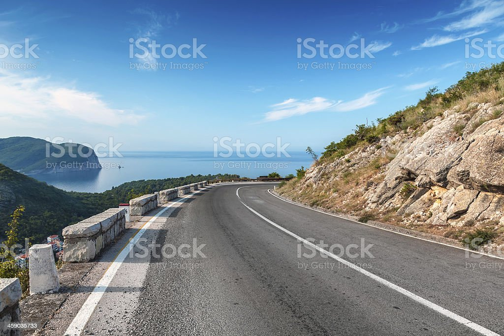 Turning mountain highway with blue sky and sea stock photo