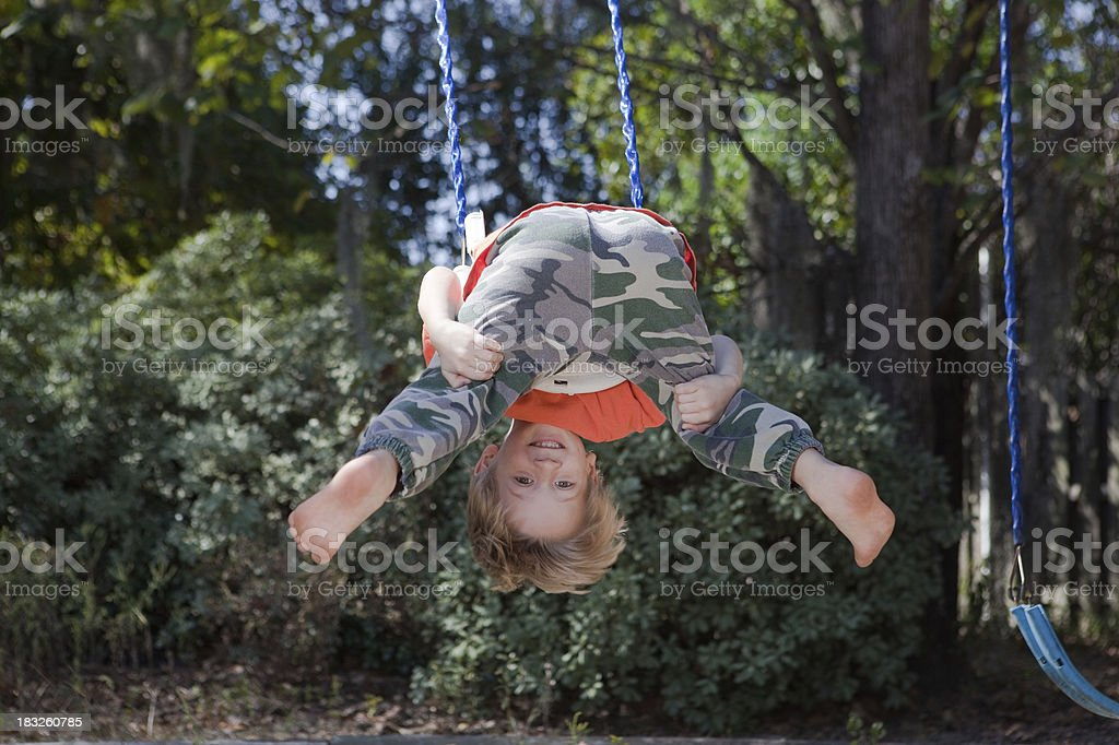 Little boys invents his own way to swing upside down.Kids can make...