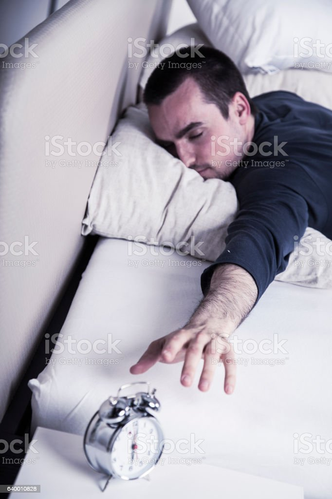 Turning off the alarm clock in the morning stock photo