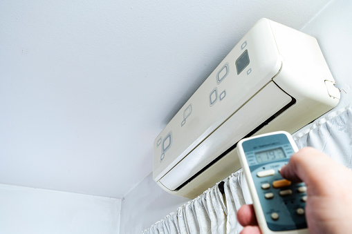 Turning on an air conditioner with the remote control. Industry concept