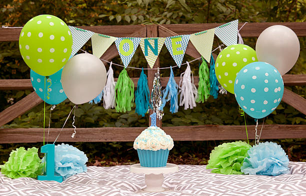 Turning One Background First Birthday scene for a child turning one. Banners, balloons, and cake and candle. first birthday stock pictures, royalty-free photos & images