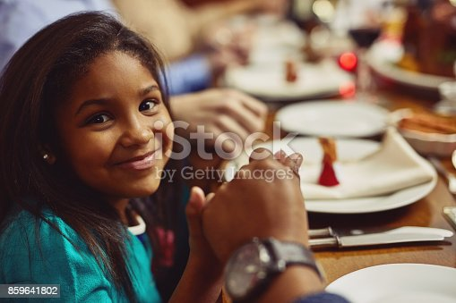 Portrait of an adorable little girl holding hands in prayer with her family before having a meal together