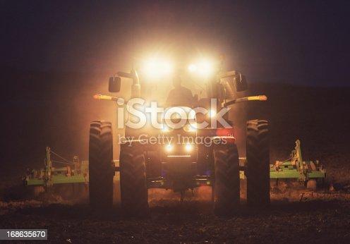 A farmer turns a field in deep twilight.  Shot at high iso, light grain.