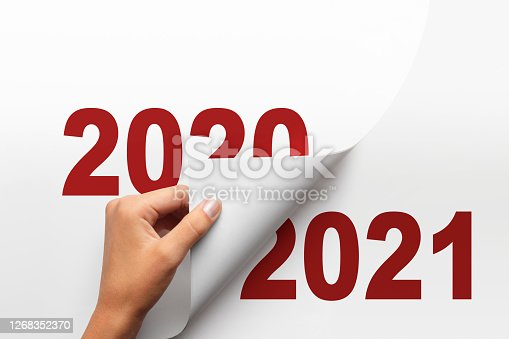 A woman turn the page from 2020 to 2021