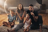 Shot of a young family relaxing on the floor and watching movies together at home