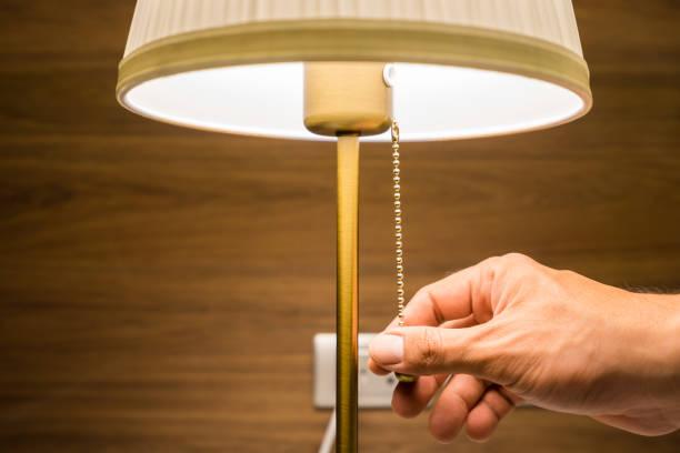 włączanie nowoczesnej lampy elektrycznej łóżka. - lampa elektryczna zdjęcia i obrazy z banku zdjęć