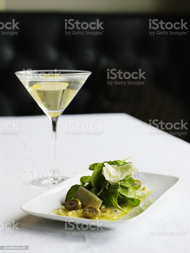 Turnip 'carpaccio' with arugula, parmesan, pine nuts and peaches, with vesper cocktail royalty free stockfoto