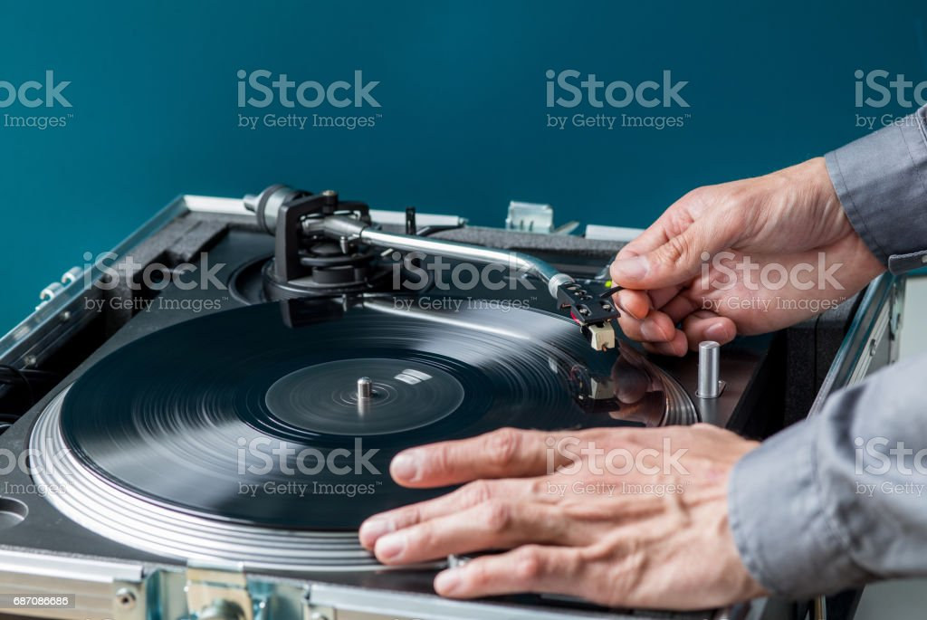 DJ Turntable and Vinyl, Hands Placing Needle on Record stock photo