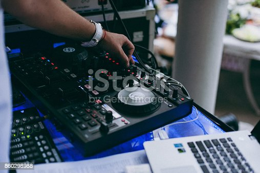 istock DJ turntable console mixer controlling with two hand in concert nightclub stage. 860298988
