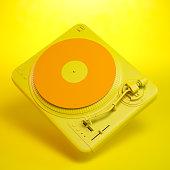 Orange and yellow turntable on yellow background