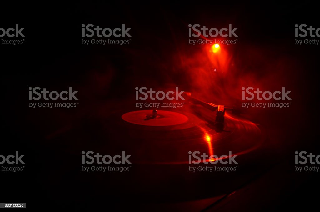 Turntable playing vinyl with glowing abstract lines concept on dark background. Selective focus stock photo