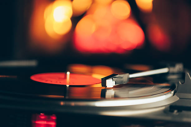 turntable with lp vinyl record against burning fire background - records stock photos and pictures