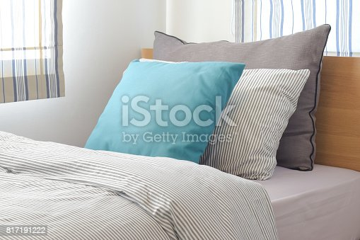 istock Turquoise and gray pillow on bed with stripe pattern bedding style 817191222