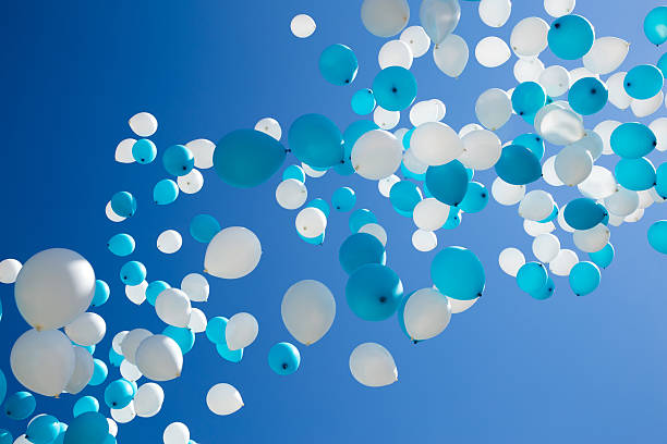 turquoise and white balloons in sky stock photo