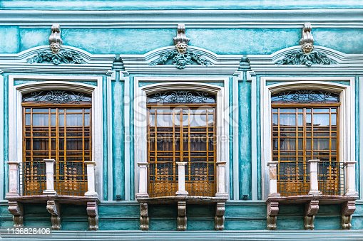 Close up of a turquoise colonial style facade in the historic city center of Cuenca, Ecuador, South America.