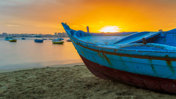Turquoise blue fishing boat on the beach at sunrise with Alexandria skyline in far distance and colorful sky at sunrise stock photo